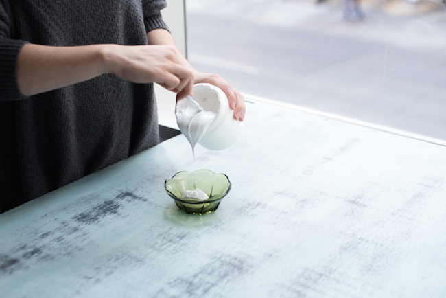 pouring gesso into a small green bowl