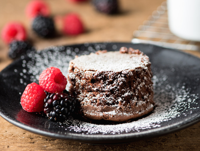 Single serve chocolate cake with berries and powdered sugar
