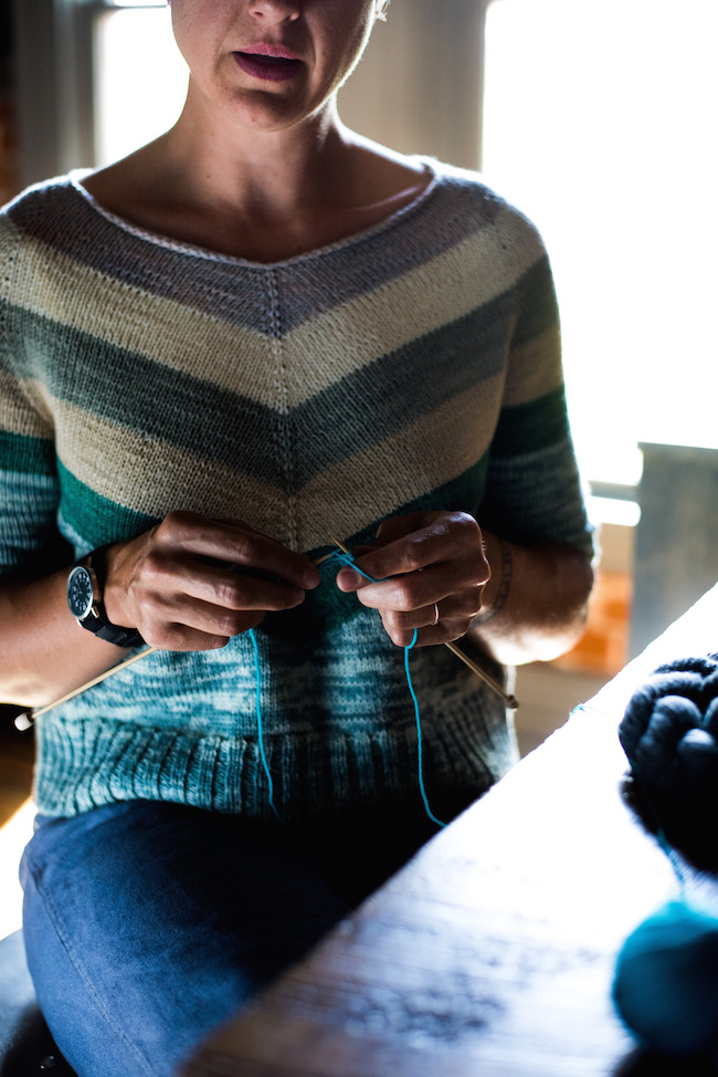woman knitting while wearing knit sweater