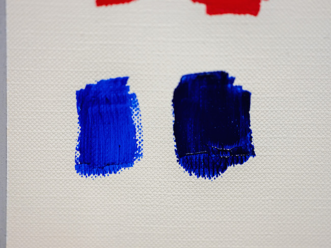 Blue paint from the tube next to blue paint mixed with a touch of red