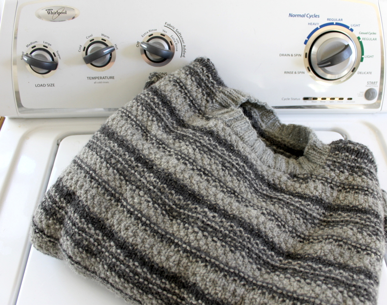 Gray striped knit sweater on top of a washing machine
