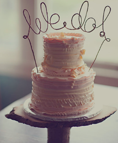 "Tiered Pink Cake with Topper Reading ""We Do"""