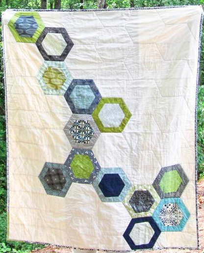 white quilt featuring colored hexagons