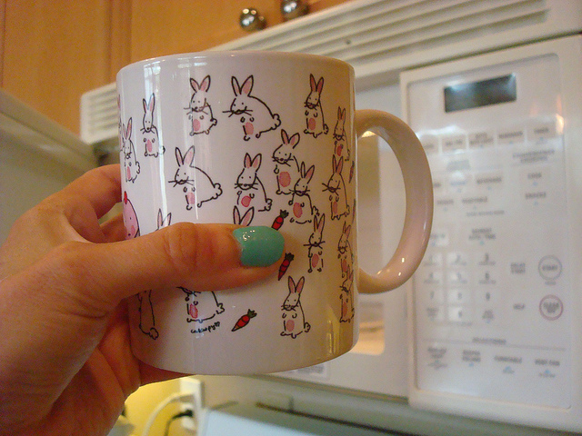 Hand Putting Mug into Microwave