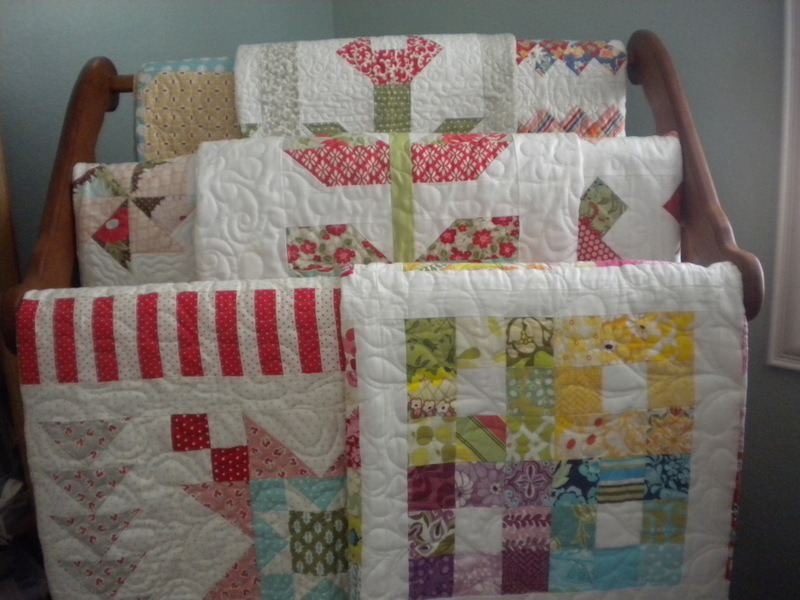 Multiple Quilts Hanging on a Wooden Rack