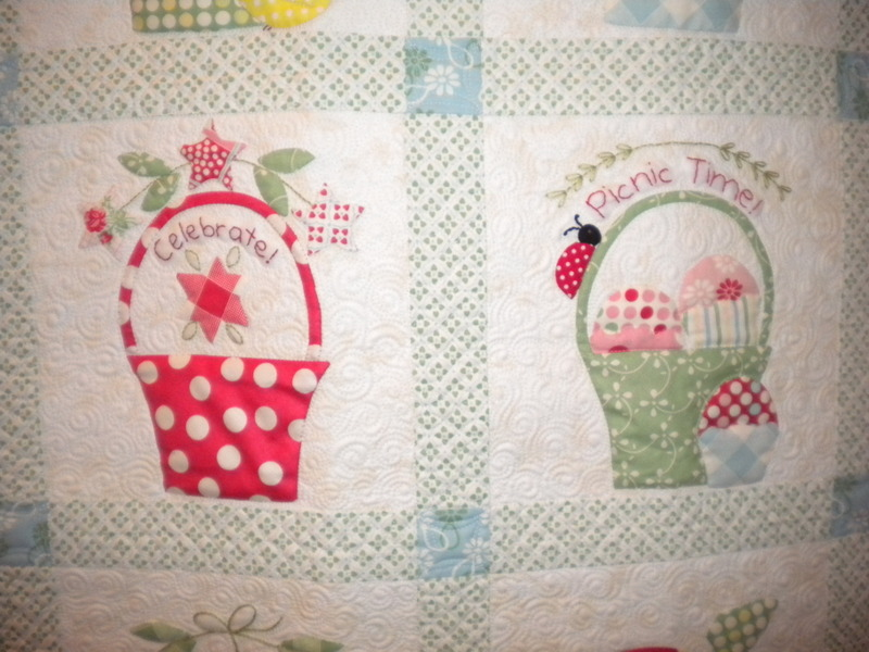 "White Quilt Featuring Pattered Baskets Reading ""Celebrate!"" and ""Picnic Time"""