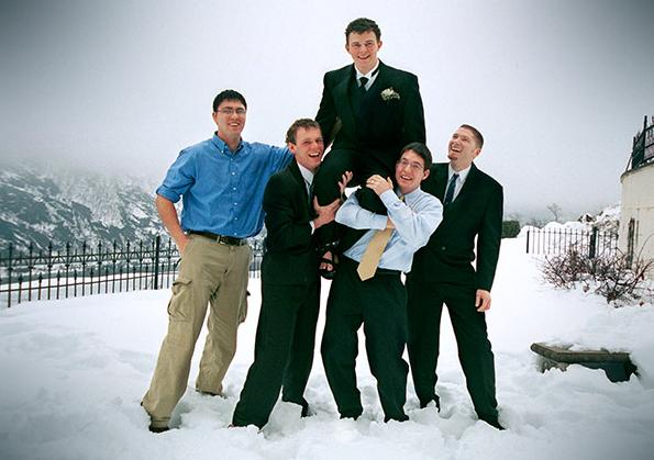 Groomsmen Holding Groom on Shoulders in Snow