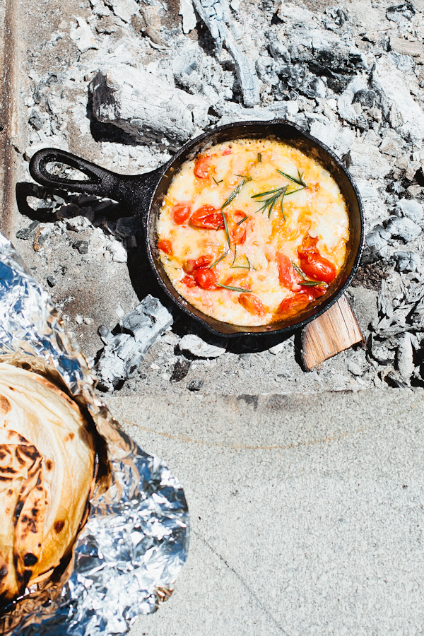 Eggs, Tomatoes and Herbs in Cast Iron Skillet Over Campfire
