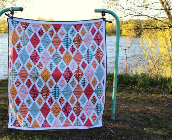 Colorful Diamond-Patterned Blanket Hanging Against Natural Background