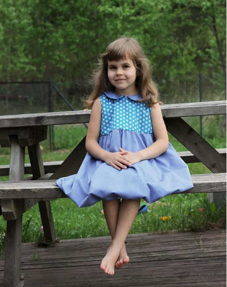 Little Girl Wearing Blue Dress, Sitting on Picnic Bench