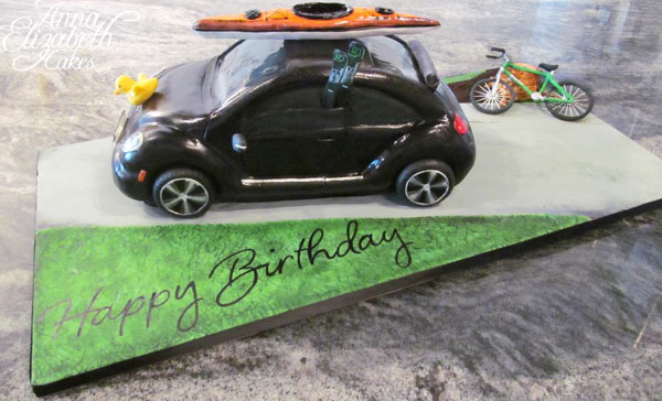 Cake in Shape of Little black Car with Surfboard on Top