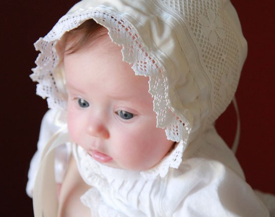Baby Girl Wearing White Dress and Bonnet