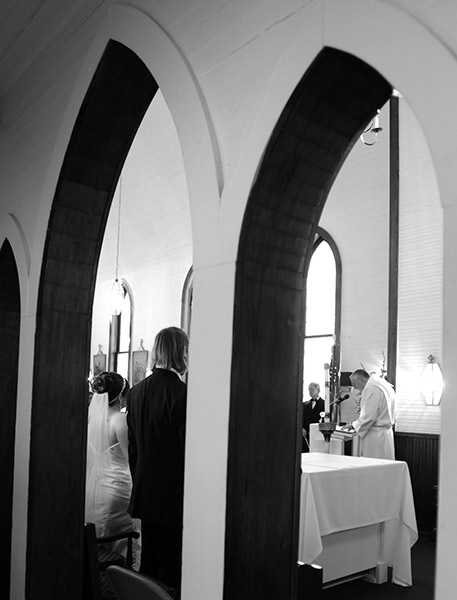Black and White Artistic Photo of Wedding Scene Through Archways