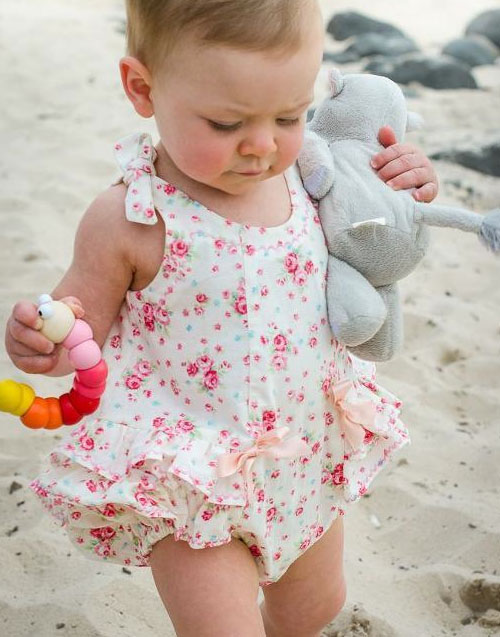 Baby Wearing Romper and Carrying Stuffed Animal