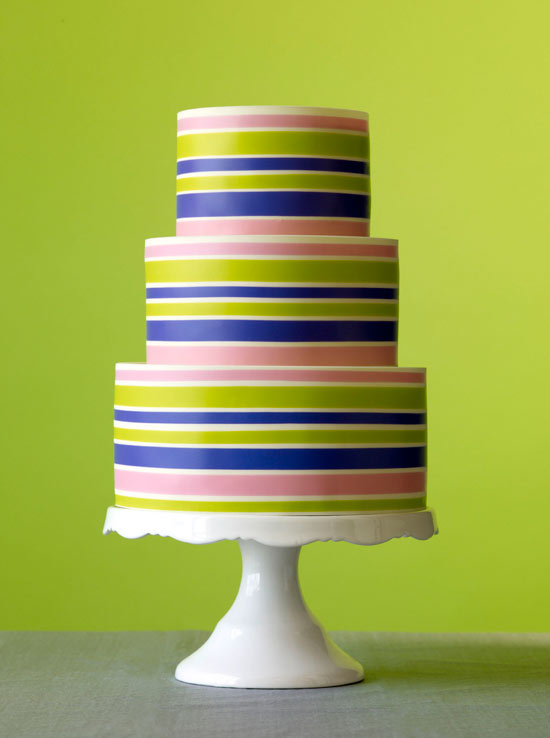 Colorful Striped 3-Tier Wedding Cake Against Bright Green Background
