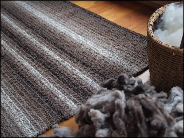 Striped Grey-Toned Knit Rug Next to Basket and Yarn