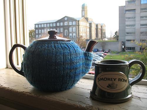 Tea Pot Covered in Knit Mitten, Sitting Next to Mug