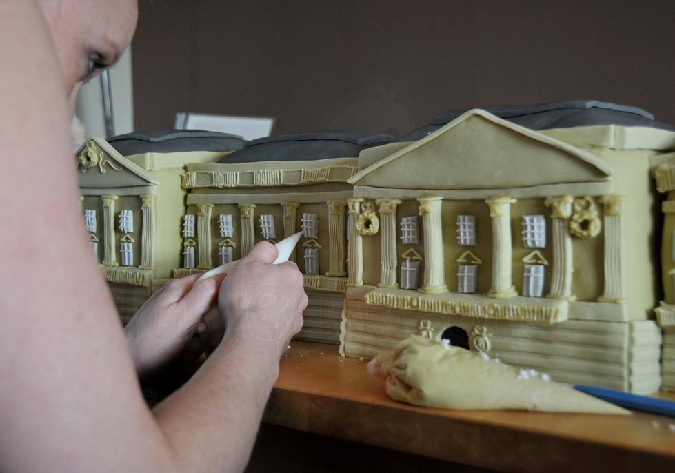 Woman Piping Detail onto Buckingham Palace Cake
