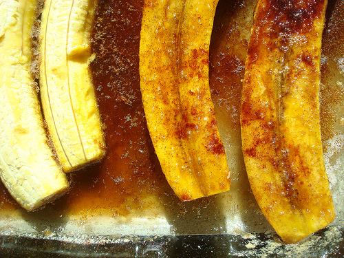 Plantains in Baking Dish in the Process of Being Flipped