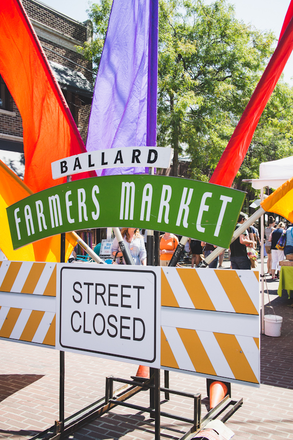 Entrance to Farmers Market with Colorful Flags and Large Sign