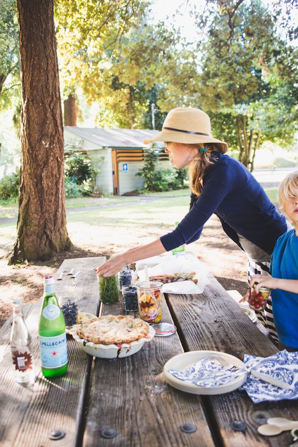 Woman in Hat Reaching Over Picnic Table
