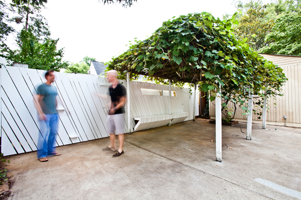 Shot of Two Blurry Men Standing Against a White Fence