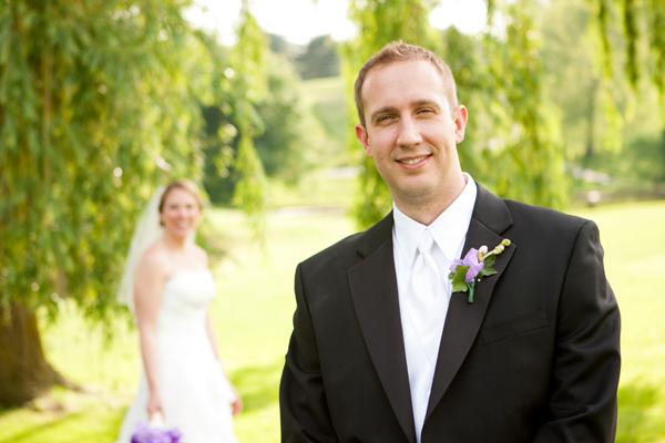 Smiling Groom, Bride Blurred in Natural Background