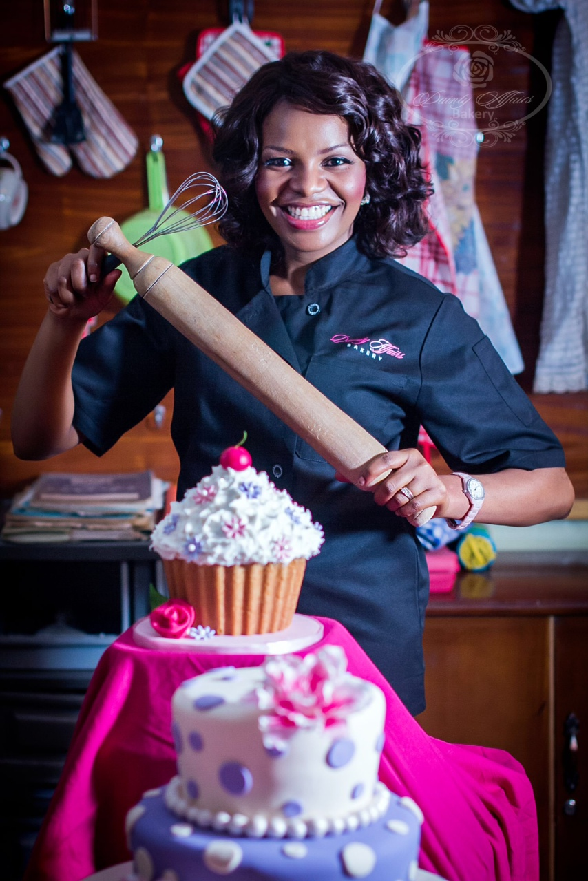 Lolade Ogunjimi Standing with Rolling Pin Behind Her Cakes