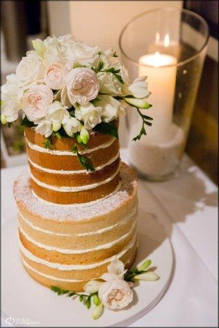 Naked Cake Topped with White Flowers, Next to Candle
