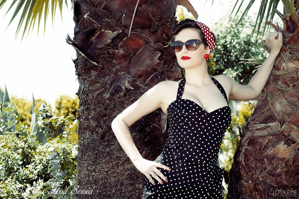 Woman in Polka Dot Bombshell Dress Leaning Against Palm Tree