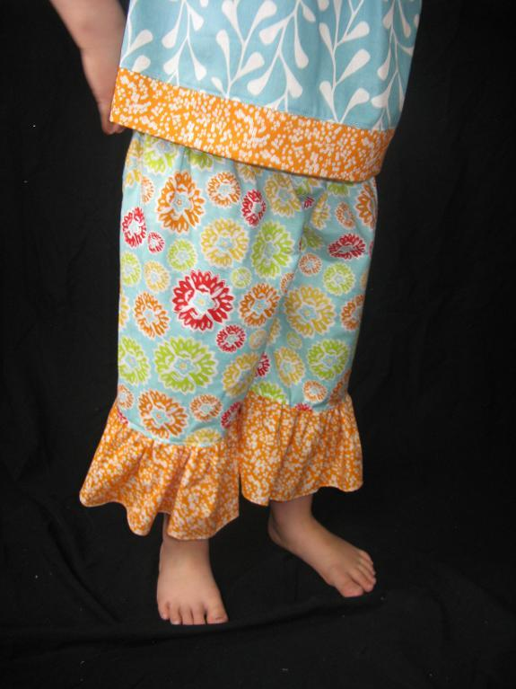 Little Girl Modeling Colorful Pants with Ruffle on Bottom