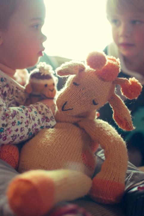 Baby Holding Stuffed Knit Giraffe