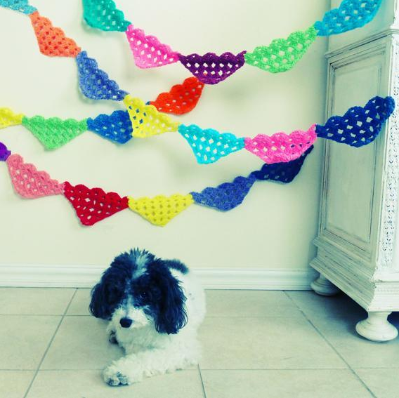 Cute Dog Sitting Below Strands of Quilted Garlands