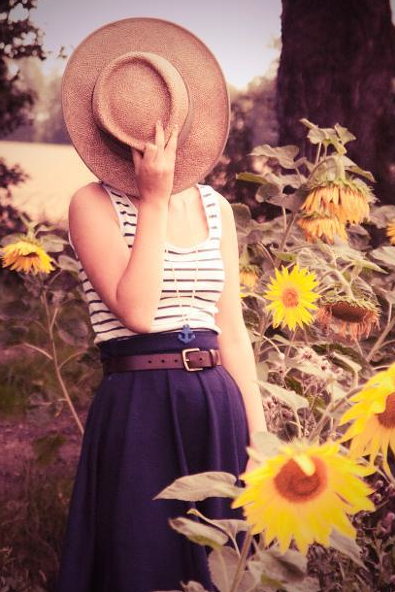 Woman in Sunflower Field Modeling Nautical Skirt, Holding Hat Over Face