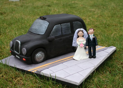 Cake Featuring Bride and Groom Figurines Next to London Cab