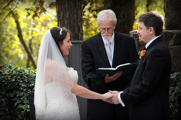 Preacher Reading to Bride and Groom Holding Hands