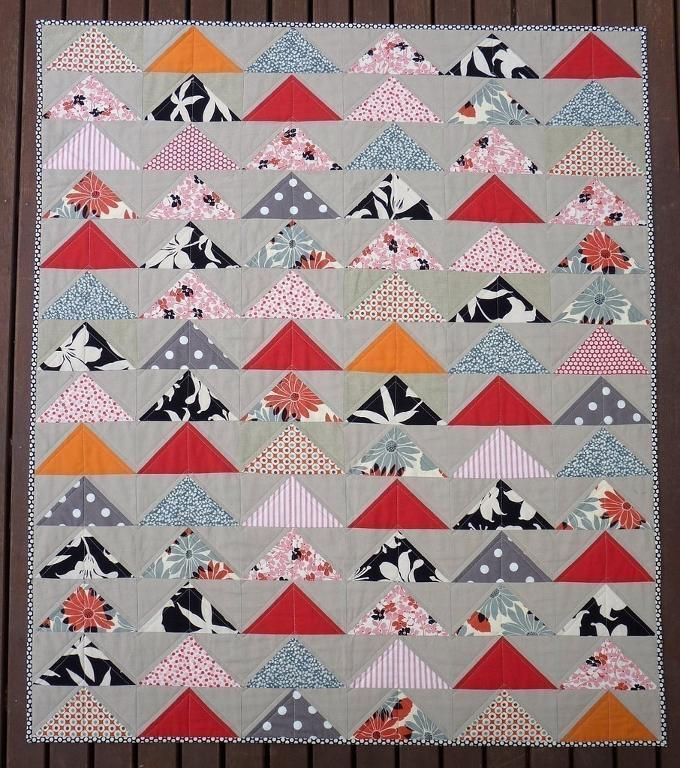 Quilt Featuring Multicolored Flying Geese Against Grey Background