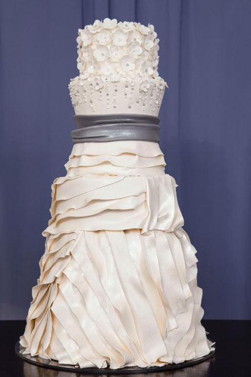 Tiered Wedding Cake with Ruffles and Flowers, Resembling Very Clearly a Wedding Dress
