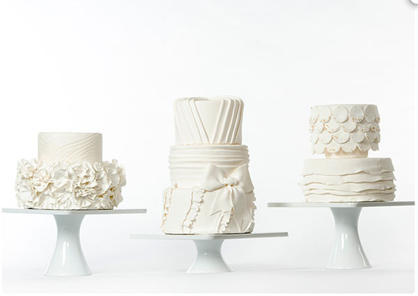 Three White Bridal Cakes, Each Uniquely Textured, on White Stands