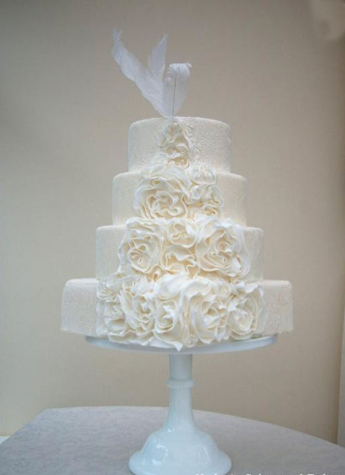 Cream-Hued Wedding Cake with Ruffled Roses and Feathers