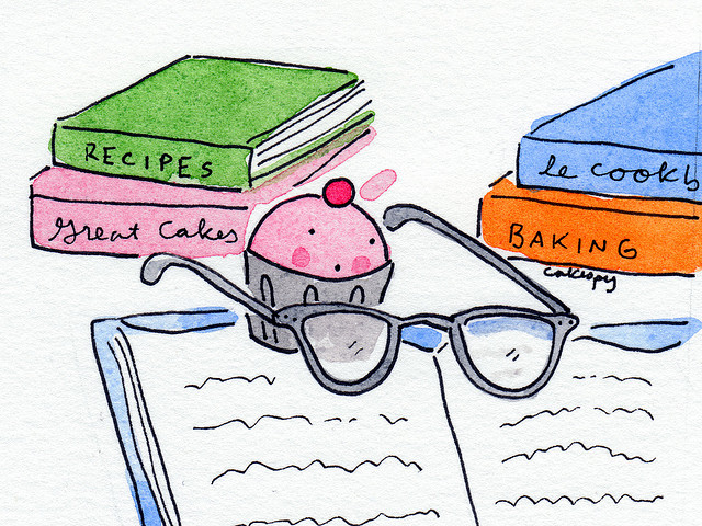 Cartoon of Cupcake Using Glasses to Read a Cookbook