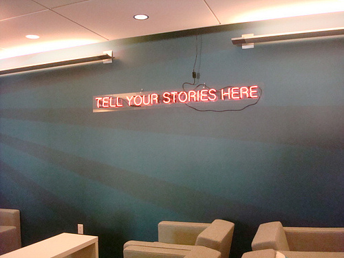 "Neon Sign Reading ""Tell Your Stories Here"""