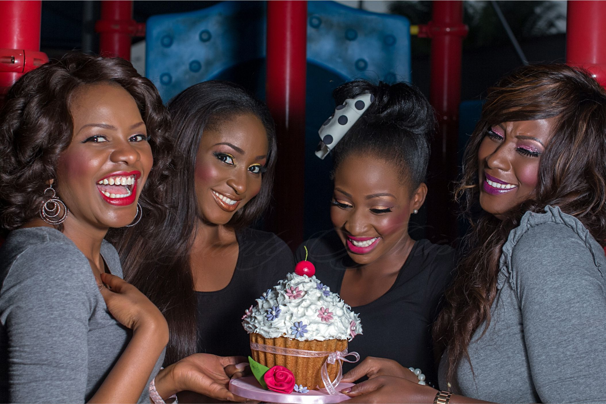 Four Woman Laughing and Holding Cake