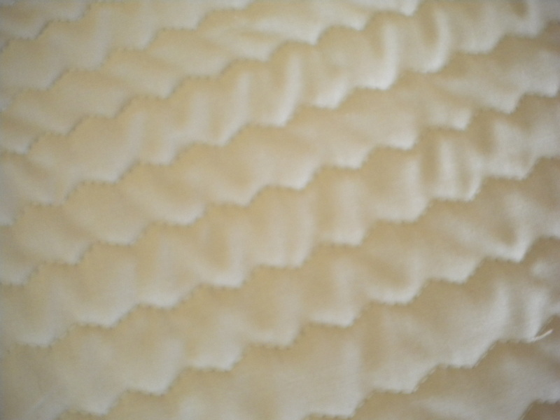Cream-Colored Quilt with Wavy Line Design
