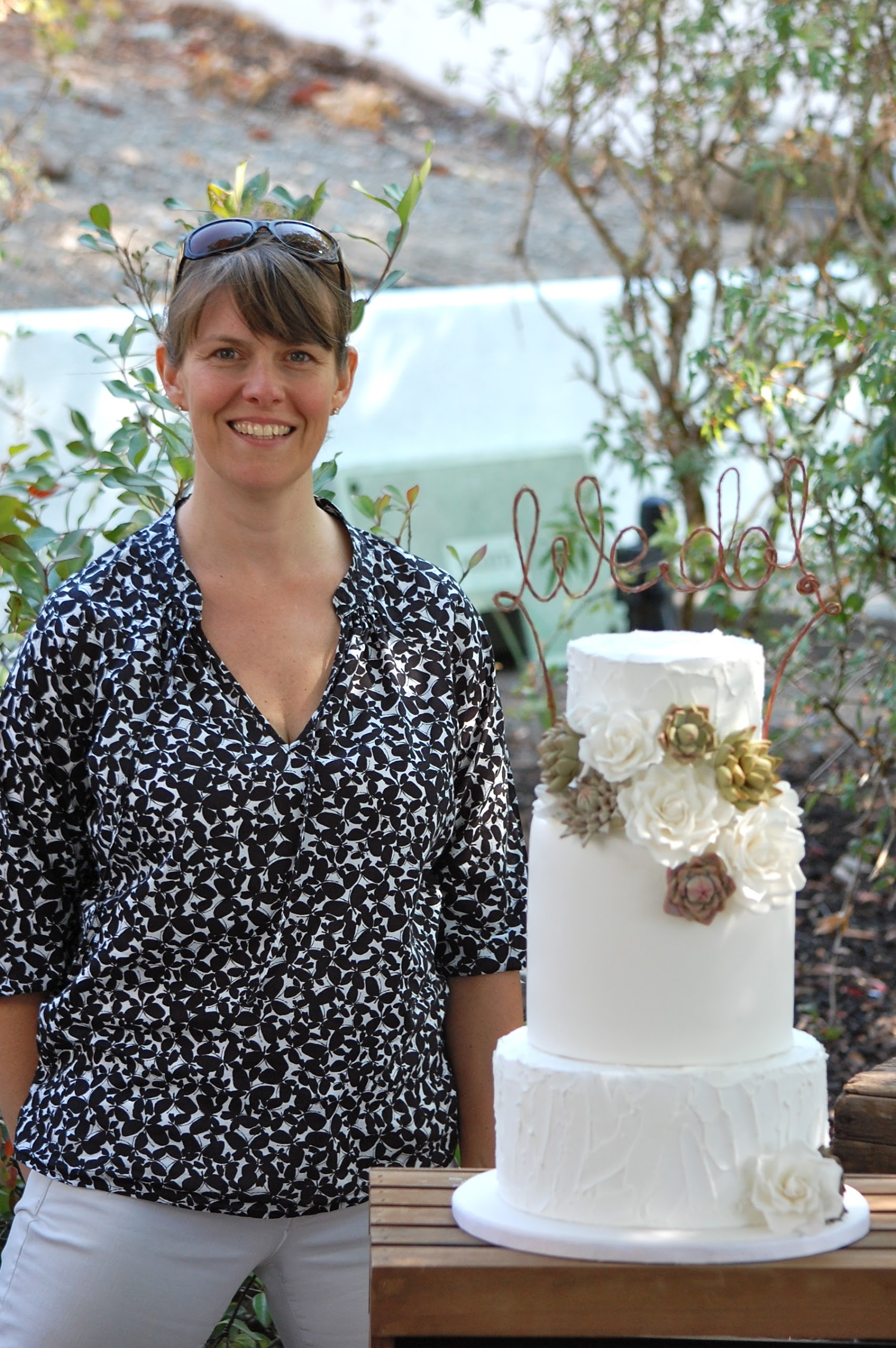 Cake Designer Standing Beside a Beautiful Finished Cake