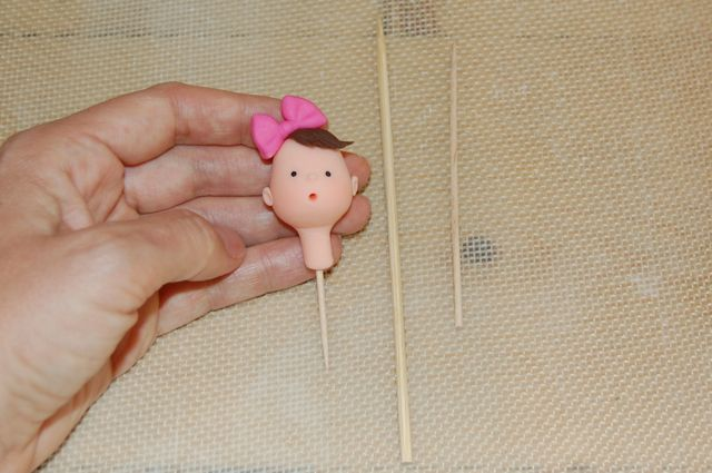 Hand Holding Fondant Head with Wooden Toothpick