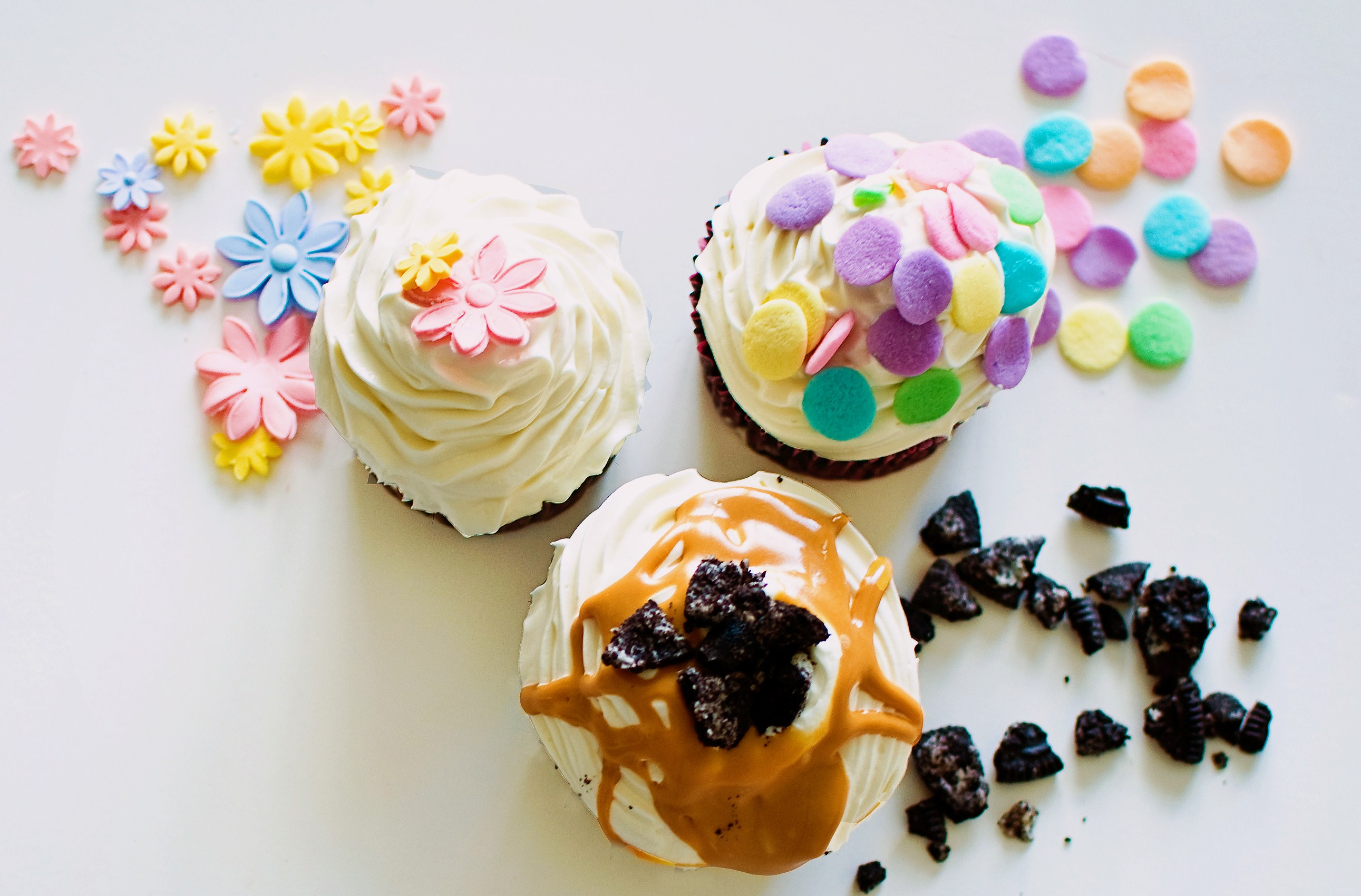 Different Cupcakes Next to An Array of Sprinkles