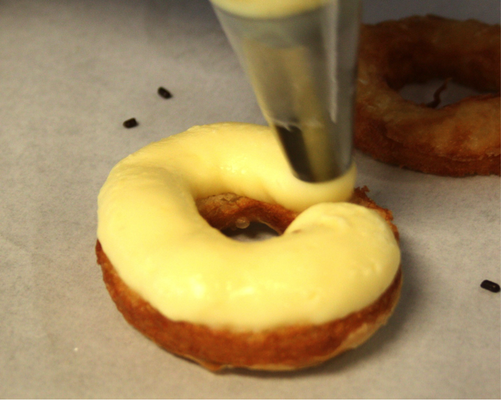 Cronut Being Iced with Yellow Icing