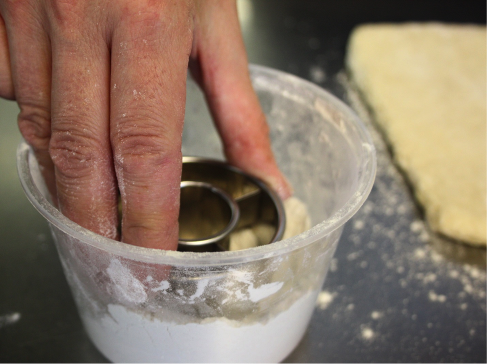 Woman Dipping Cutter into Dish of Flour