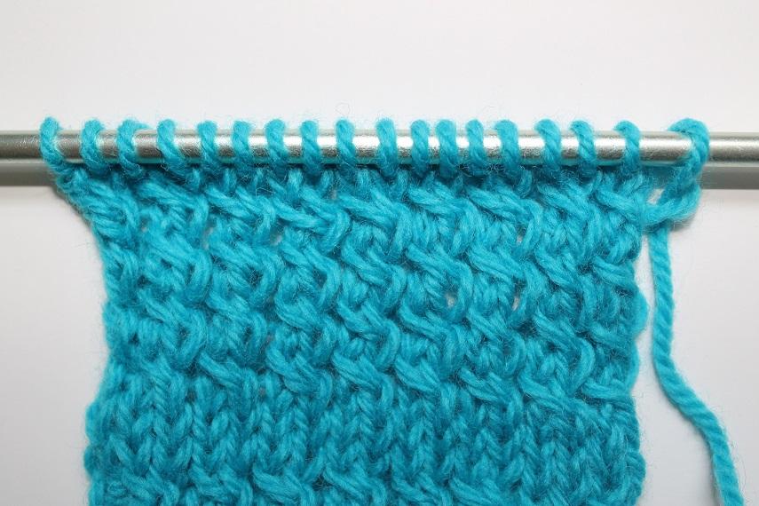 Close Up of Knit Blue Yarn on Knitting Needles